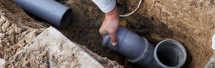 A plumber placing the tube in the ground.
