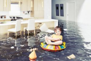 A boy riding in his pillow inside a flooded room.