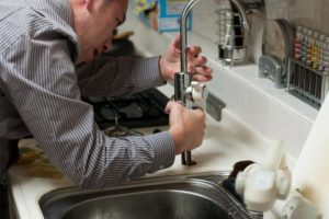 A man in a stripe sleeve installing a faucet in the sink.