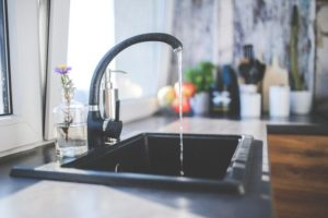 Over flowing water on a black faucet.