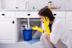 Girl in a yellow gloves talking to the phone beside a damaged sink pipe.