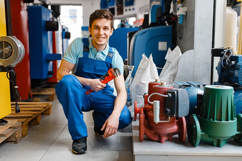 A plumber smiling while holding a wrench.