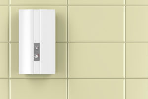 A white tankless water heater hanging in tiles wall.