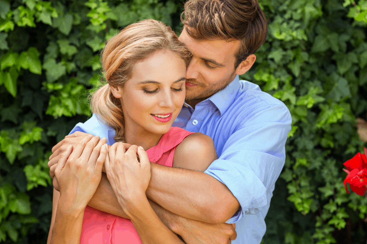 A man on a sky blue polo hugging the girl in a pink casual dress.